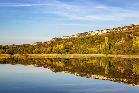 Colorful tree line on a calm lake at sunrise during autumn. Reklamní fotografie