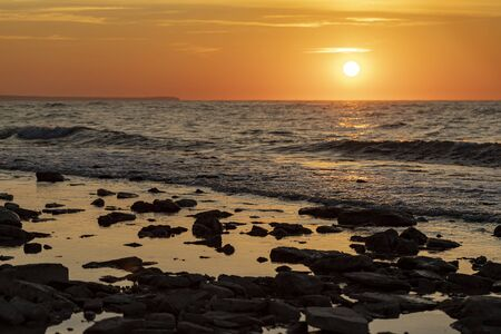 Stunning morning seascape with sun and stones on the water