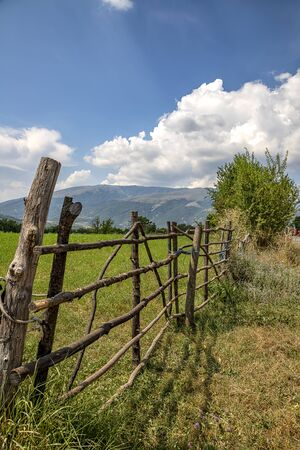 A handmade wooden fence made of thin rods. The old fence of tree trunks, rural landscape, nature wallpaper background. Reklamní fotografie