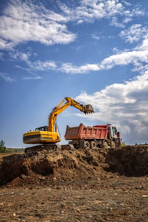 Yellow excavator and empty dump truck working at the construction site. Vertical view