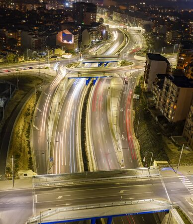 Beautiful night traffic junction road with lights of vehicle movement aerial view from drone. Vertical view