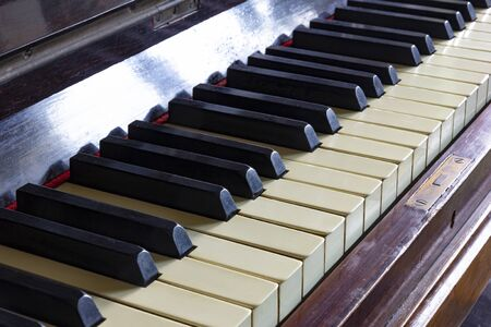 Close up of black and white keys of a vintage piano. Selective focus