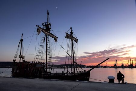 Silhouette photo of sailing ship moored in the port and fisherman in the evening