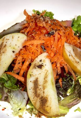 Fresh salad with lettuce, carrots, red beets, chopped apples with dressing in a ceramic plate. Vertical view Reklamní fotografie