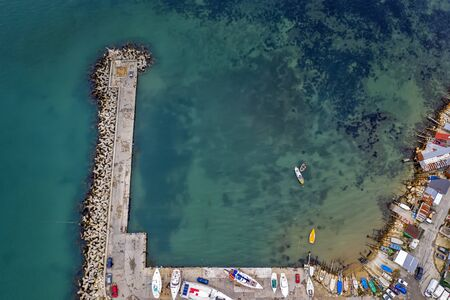 Top view from drone to the pier and the marina with boats and yachts. Sea landscape with fishing houses from above