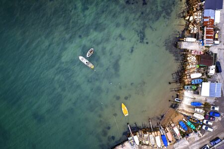 Top view from drone to the pier and the marina with boats and yachts. Sea landscape with fishing houses from above.