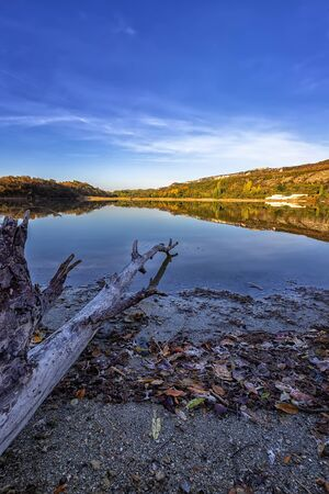 Vertical view from the shore of old and mountain hills with autumn colors reflected in still lake water
