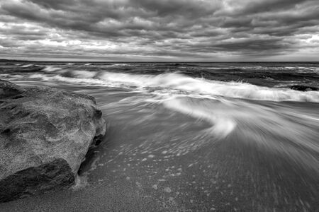 Stunning black and white long exposure seascape with big rock and motion blur waves.