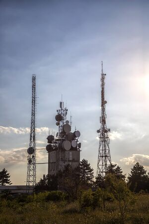Mobile communication tower with control devices and antennas, transmitters, mobile communications, and the Internet at sunset