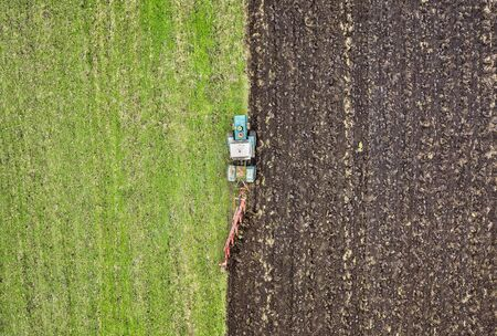 Agriculture. Farming. Tractor working in field. Aerial view. Tractor cultivating field. Copy space.