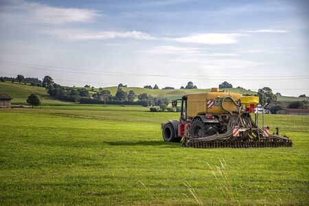 Application of manure on arable farmland with the heavy tractor who works at the field in Germany Stock Photo