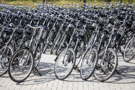 Bicycle parking station full of bikes. Many parked bicycles.