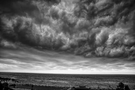 Dramatic stormy clouds over the sea. Black and white view