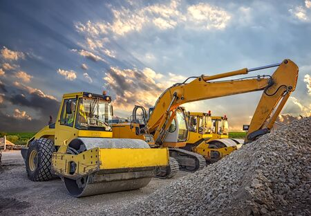 Parked drum roller and excavators at the construction site, after work Imagens