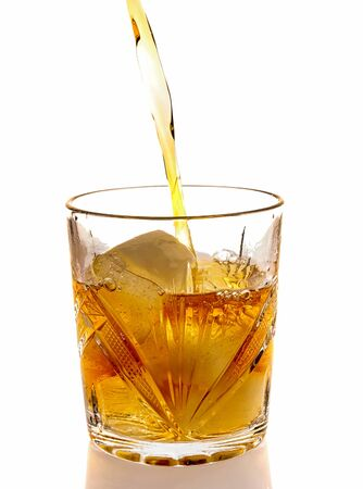 Pouring whiskey in a glass with ice. front view. Isolated