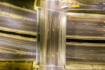 Beautiful night traffic junction road with lights of vehicle movement aerial view from drone.