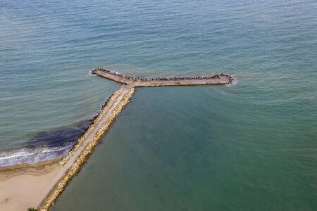Aerial view from drone of the sea, beach and wave breaker stones