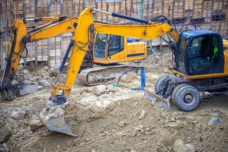 Heavy construction equipment working at the construction site. 스톡 콘텐츠