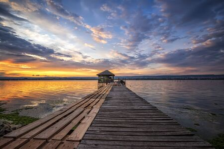 Exciting colorful long exposure landscape on a lake with a wooden pier and small house in the end. Archivio Fotografico