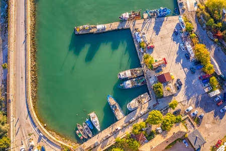 Aerial top view from drone to the seacoast and small marina with boats and yachts. Sea landscape with yachts from above Stock Photo