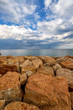 Colorful stones on a shore with fluffy clouds at the horizon. Vertical view Archivio Fotografico