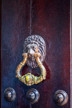 Door knocker. Old antique brass knocker on the wooden doors for knocking. Close up 版權商用圖片