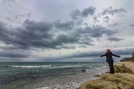 A woman on the top of a rock enjoys the view of sea and cloudy sky