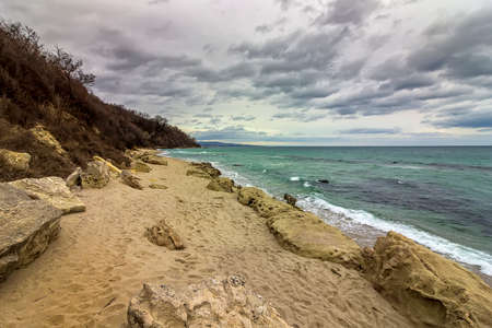 scenic view at a stony beach with cloudy sky