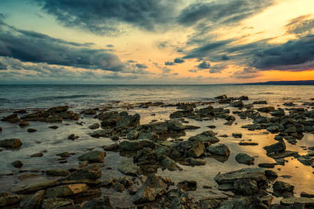 Stone beach at sunset. Twilight sea and sky. Dramatic sky and clouds. Nature landscape.