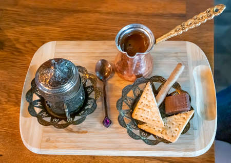 Turkish coffee being made in a traditional way with sweets.  Traditional serving coffee