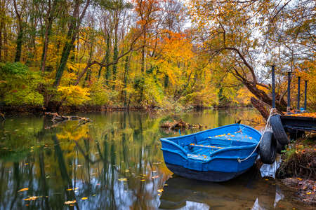 Boat with water reflection in the colorful autumn at a river pier