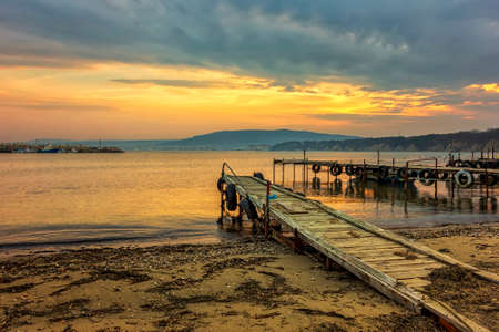 Amazing idylic sunset or sunrise at a shore with wooden piers
