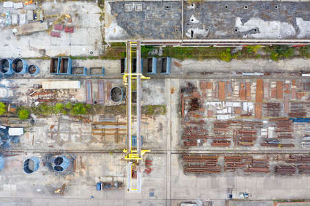 aerial view from drone of factory warehouse of steel elements and crane