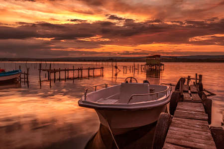 mood and tranquility at a lake shore with a boat at a wooden pier