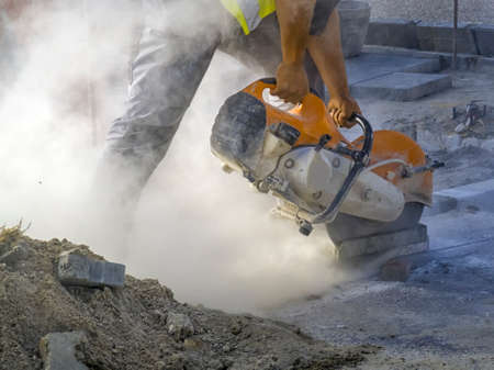 A worker cuts a tile to size with an electric grinder with many smoke. Pollution concept 版權商用圖片