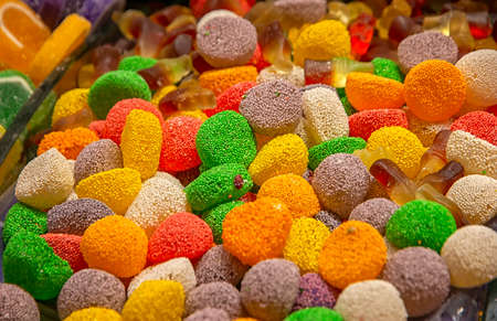 Many colorful sweets with sugar and flavor fruit. Horizontal view.