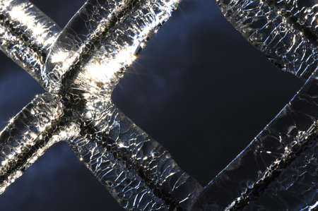 Frozen water droplets trapped on a chainlink fence Stock Photo
