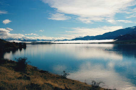 Calm morning on a lake in New Zealand with Southern Alps in the background Stock Photo