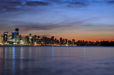 Vancouver skyline in the evening sunset across Burrard Inlet Stock Photo