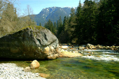 Large boulder on the edge of the Seymour River in North Vancouver, Canada Stock Photo