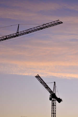 Silhouette of cranes above a building site at sun rise Zdjęcie Seryjne
