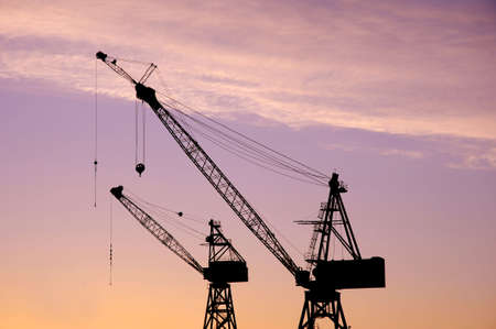 Silhouette of cranes above a building site at sun rise Stock Photo