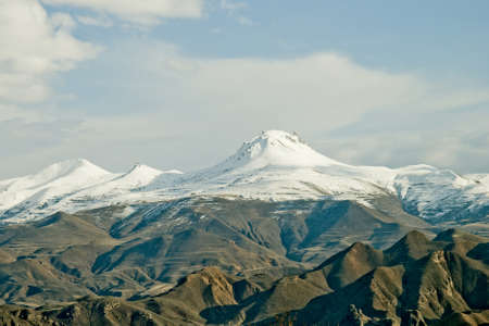 peerless: snowy mountains whose peaks shining in the setting of solar rays Stock Photo