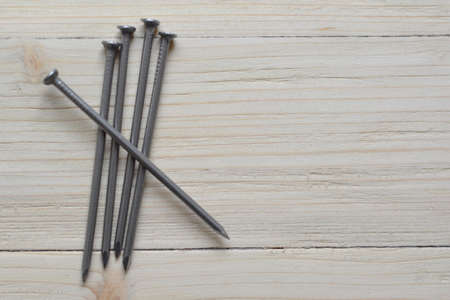 On a worn-out stick, four nails are stacked side by side. The fifth is placed on them 스톡 콘텐츠