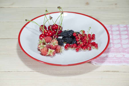Delicious ecologically clean currant raspberry cherry and mulberry beautifully placed on a plate with white red ribbon 스톡 콘텐츠