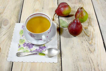 A beautiful cup of tea is lying on a table made of worn-out shoes, there are also three delicious pears on the table