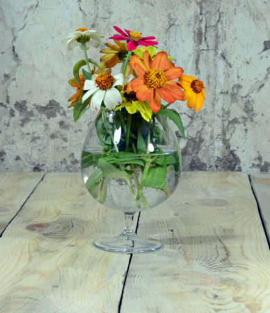A bouquet of beautiful flowers is placed in a beautiful glass cup filled with water, which is placed on a table made of worn wood.