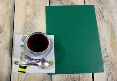 A beautiful cup of iced tea is placed on a table made of worn wood, on the table there is a teaspoon and a napkin. 스톡 콘텐츠