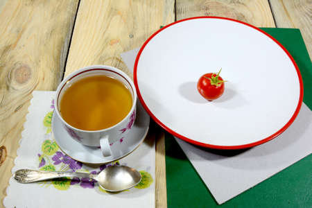 A cup of tea filled with tea is framed on a wooden table with a red tomato on a white plate.