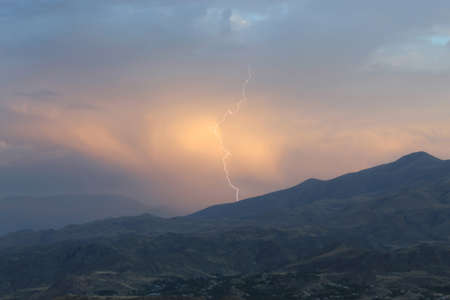 A very beautiful view of the sunset when the lightning strikes against the backdrop of clouds on the mountains